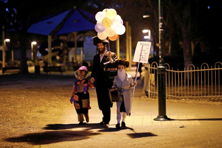 Image: An Ultra Orthodox Jewish family dressed in costumes walk during the Jewish holiday of Purim, Israel