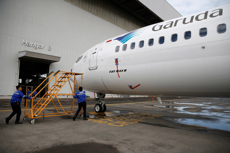 Image: Technicians carry a ladder as they prepare to check Garuda Indonesia's Boeing 737 Max 8 airplane parked at the Garuda Maintenance Facility AeroAsia, at Soekarno-Hatta International airport near Jakarta