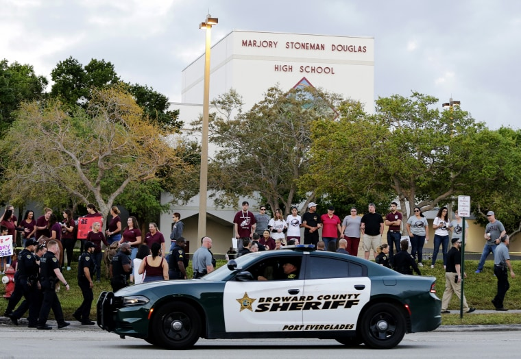 Image: A police car drives near Marjory Stoneman Douglas High School in Parkland, Florida, as students return to class for the first time after a shooting that left 17 dead on Feb. 28, 2018.