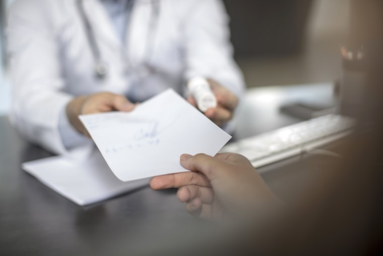 Image: Doctor giving patient a note