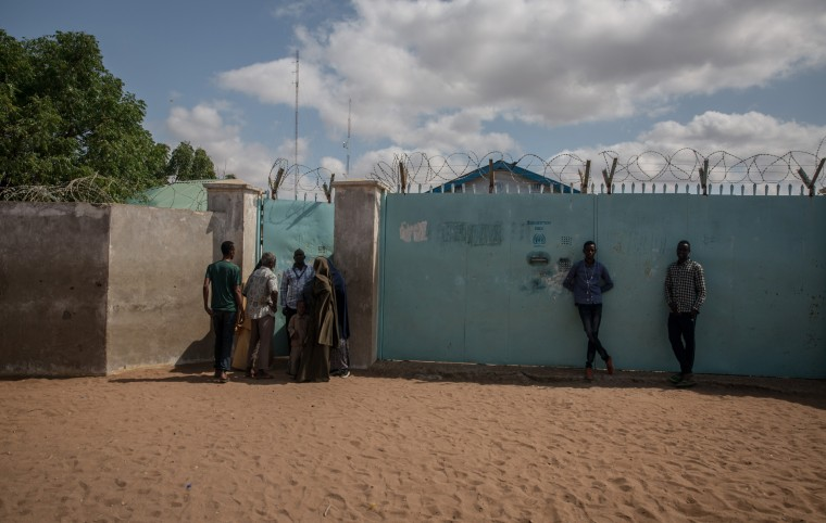 Image: Refugees crowd around a UNHCR field office in the Dadaab refugee camp.
