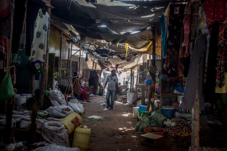 Image: A man walks through a market in the Dadaab refugee camp.