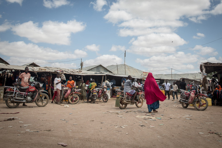 Image: A woman walks through a busy street inside the Dadaab refugee camp.