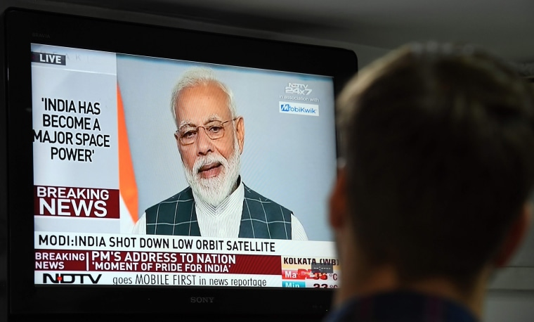 Image: A man watches Indian Prime Minister Narendra Modi's address to the nation on a local news channel in New Delhi