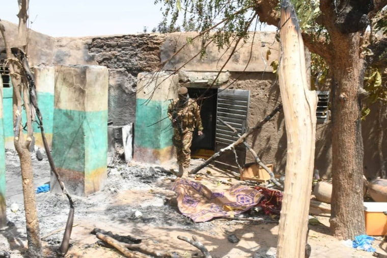 Image: A soldier walks amid the damage after an attack by gunmen on Fulani herders in Ogossagou
