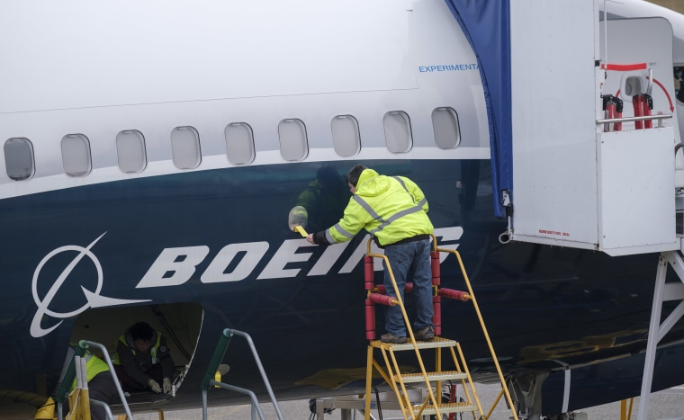 Image: An employee works on the fuselage of a Boeing 737 MAX 9 test plane outside the company's factory
