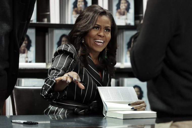 """Image: Former First Lady Michelle Obama signs books during an appearance for her book, \""""Becoming,\"""" in New York"""