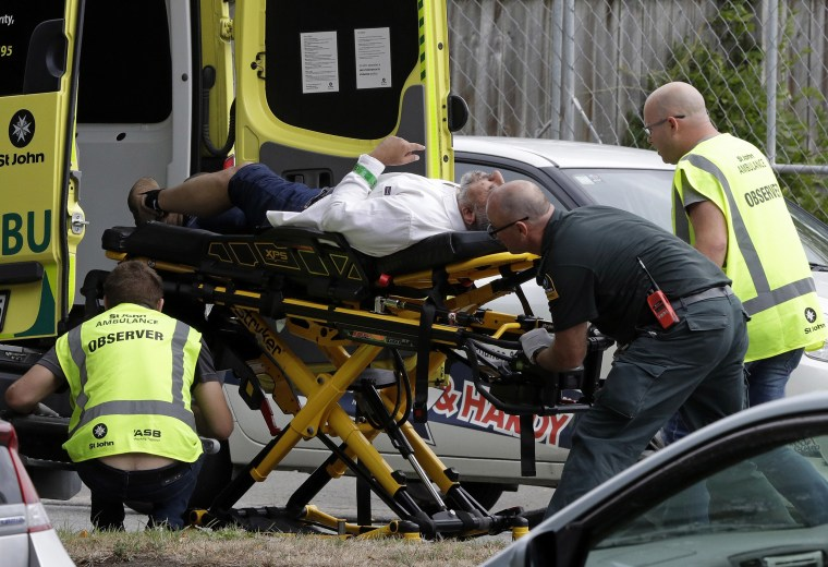 Image: Ambulance staff take a man from outside a mosque in central Christchurch, New Zealand