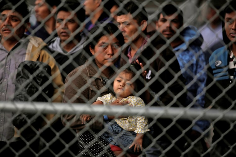 Image: Central American migrants are seen inside an enclosure where they are being held after turning themselves in to request asylum, in El Paso