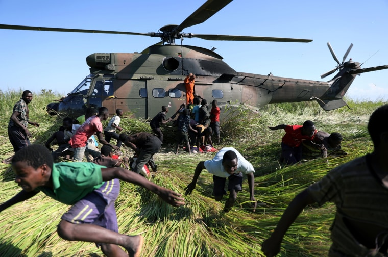 Image: People run after collecting food aid from a South African National Defence Force (SANDF) helicopter in the aftermath of Cyclone Idai in Nhamatanda