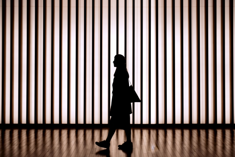 Silhouette of woman walking in front of striped illuminated wall