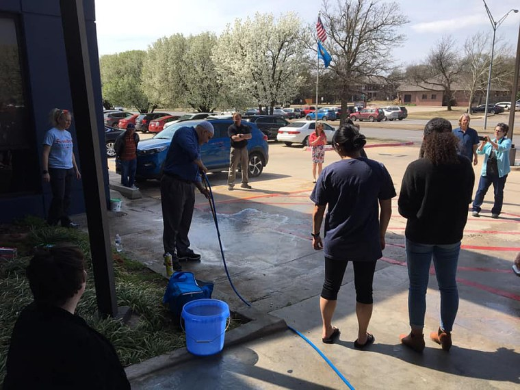 Community members help to power wash and clean swastikas and other racist graffiti found at Oklahoma City Democratic Party headquarters and Chickasaw Nation's Oklahoma City area office, on Thursday.