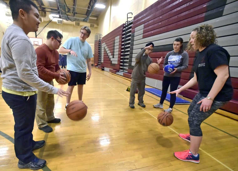 Teacher Leslie Fazzuoli, right, demonstrates dribbling during a basketball skills review with Unified Sports Special Olympics basketball athletes and their peers  in North Haven, Connecticut. The program combines students with and without disabilities on the same teams.