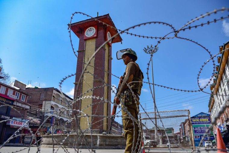 Image: An Indian army soldier stands guard in front of the clock tower during a shut down in Srinagar, Kashmir