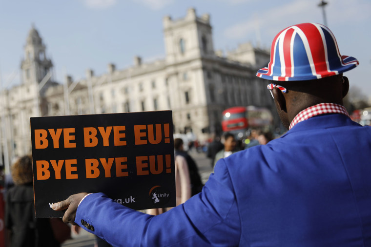 Image: Pro-Brexit activist Joseph Afrane holds a placard as he demonstrates outside the Houses of Parliament in Westminster