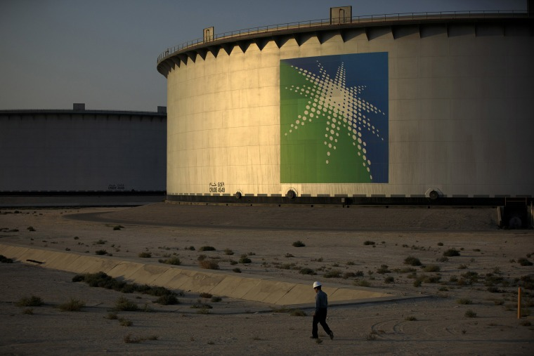 Image: An employee walks past crude oil storage tanks at the Juaymah Tank Farm in Saudi Aramco's Ras Tanura oil refinery and oil terminal in Ras Tanura, Saudi Arabia