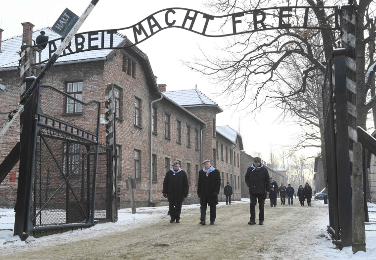 Image: People pass the main gate after the 74th anniversary of the liberation of former German Nazi death camp Auschwitz-Birkenau, in Oswiecim, Poland