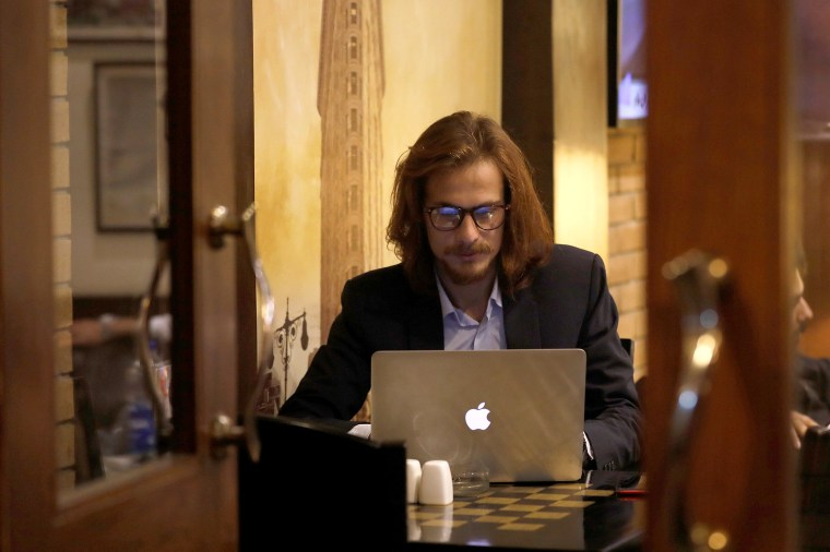Image: M Hanzala Tayyab, 24, a social media campaigner and cyber analyst, is seen working on computer at a local cafe in Islamabad,