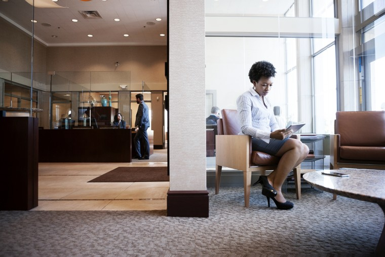 Image: Businesswoman using tablet computer while sitting on sofa in office