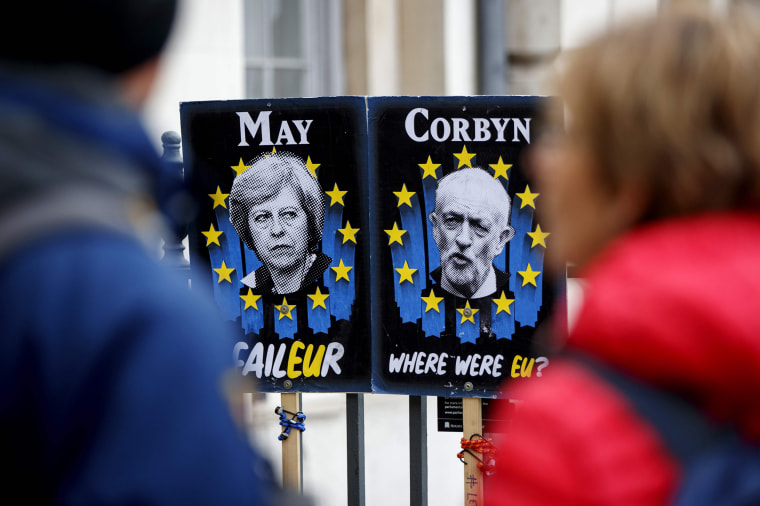 Image: Pedestrians walk past placards featuring Britain's Prime Minister Theresa May and opposition Labour party leader Jeremy Corbyn near the Houses of Parliament