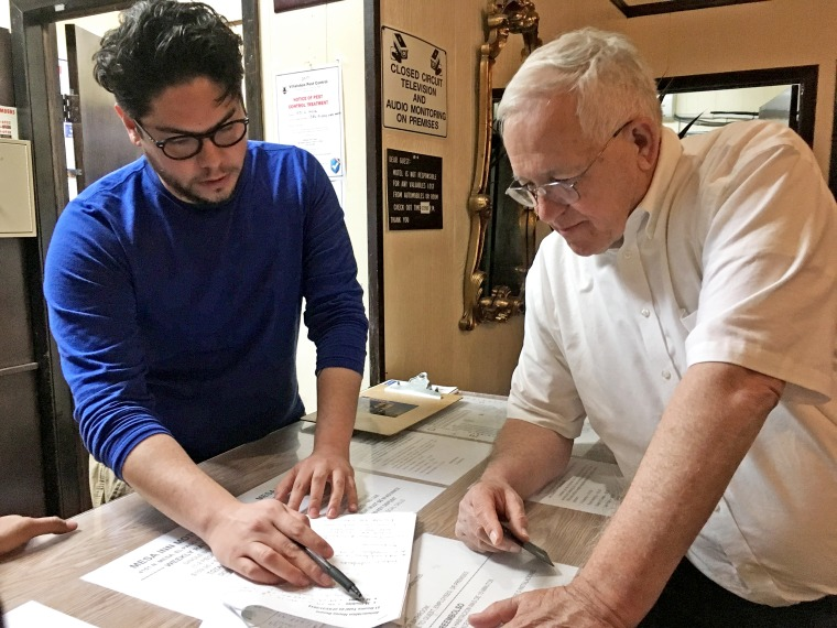 Ruben Garcia, Annunciation House executive director and founder, reviews with general manager Chris Acuna, costs of hotel rooms and ballroom space for immigrants who have come to the border and been released by Customs and Border Protection.