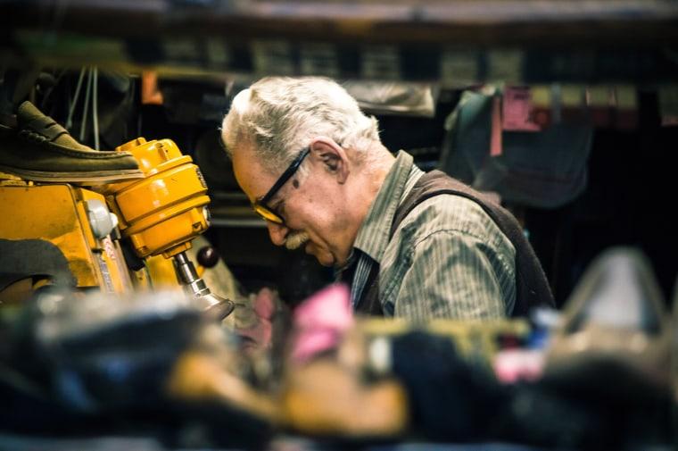 Image: Senior man in his shoe repair shop.