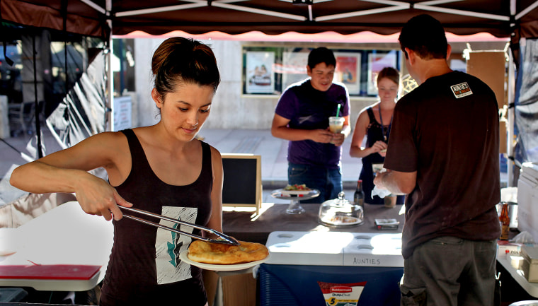 Kate Koyama, co-owner of Auntie's Native American Fry Bread, left, prepares a fry bread taco as co-