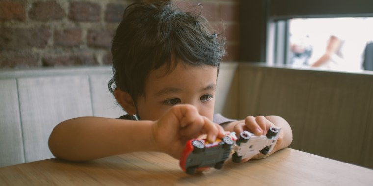 A Young boy sitting at a table in a restaurant playing with some toy cars.