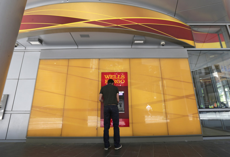 Image: A man uses a Wells Fargo ATM in Charlotte, North Carolina
