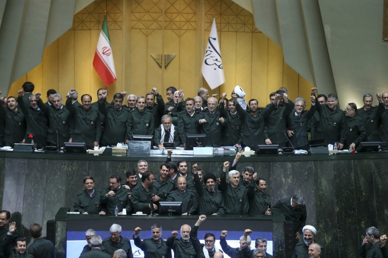 Image: Wearing the uniform of the Iranian Revolutionary Guard, lawmakers chant slogans during an open session of parliament in Tehran, Iran