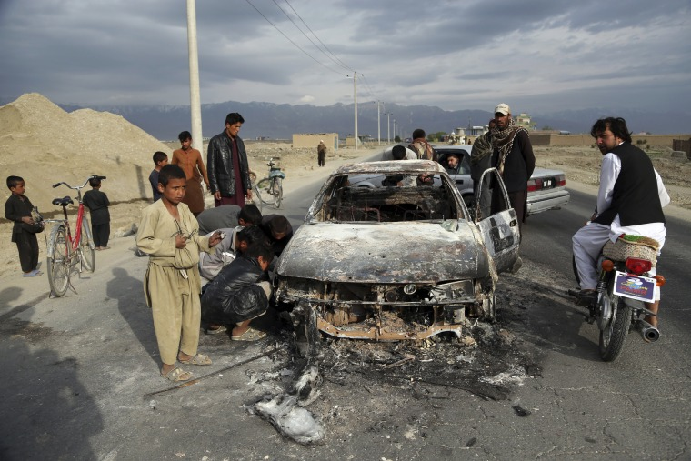 Image: A group of Afghan civilians look at a burnt vehicle near the Bagram Air Base near Kabul after a roadside bomb detonated, killing three American service members, in Afghanistan on April 9, 2019.