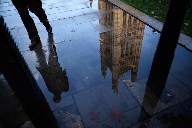 Image: The Houses of Parliament is reflected in an puddle in London, England.