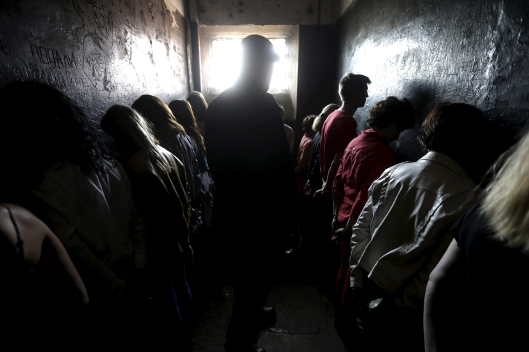 Image: People line up facing the walls as they attend a voluntary imprisonment session in the former military prison in Karaosta in Liepaja