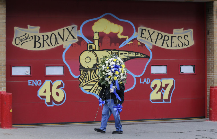 Image: A man brings flowers to a firehouse in memory of firefighter Christopher Slutman in the Bronx, New York, on April 9, 2019. Slutman was killed by a roadside bomb in Afghanistan on April 8.