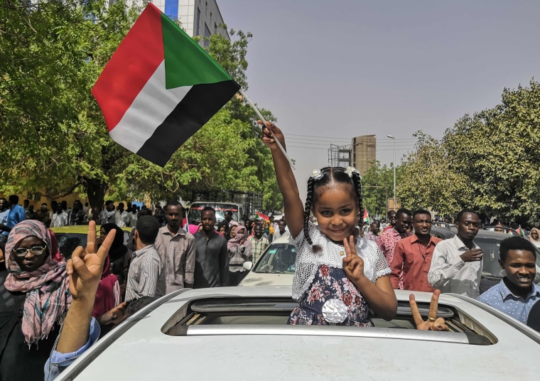 Image: A Sudanese girl flashes the victory sign and holds the national flag during a rally near the military headquarters in the capital Khartoum