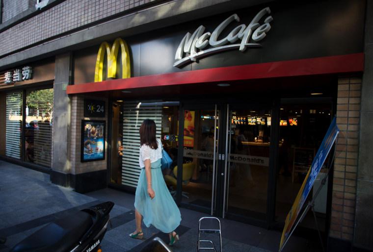 A woman walks past a McDonald's restaurant in Shanghai