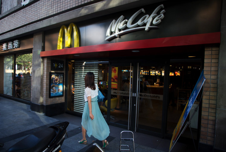 A woman walks past a McDonald's restaurant in Shanghai