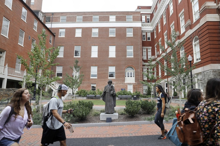 Image: Students walk past a Jesuit statue in front of Freedom Hall, center, formerly named Mulledy Hall, on the Georgetown University campus in Washington