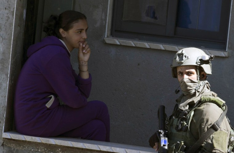 Image: An Israeli soldier walks past a Palestinian girl