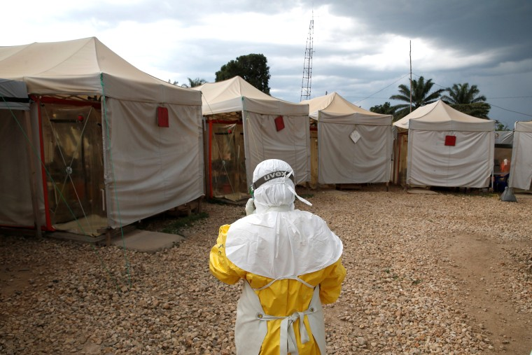 Image: A health worker wearing Ebola protection gear, walks before entering the Biosecure Emergency Care Units at the Alima Ebola treatment centre in Beni