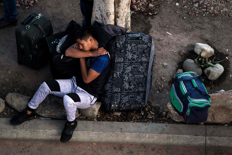 Image: An asylum seeker rests outside El Chaparral port of entry while he waits for his turn to present himself to U.S. border authorities to request asylum