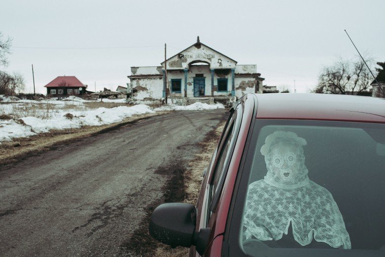 Image: Artist Alisa Gorshenina sits in a car with an abandoned House of Culture on the background in her native village of Yakshina