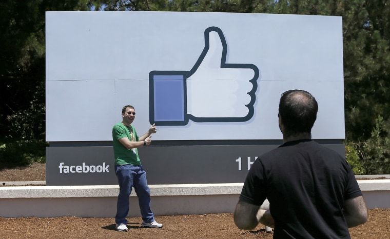A man poses for photos in front of the Facebook sign on the company's campus in Menlo Park, California, in 2014.