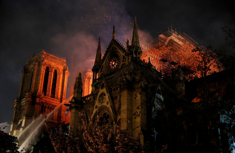 Image: Firefighters continue to extinguish flames at the Notre Dame Cathedral in Paris on April 15, 2019.