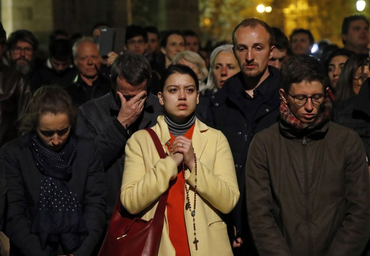 Image: People pray as the Notre Dame cathedral burns in Paris on April 15, 2019.