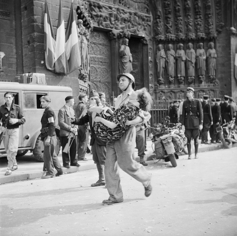 Image: A French soldier carries a woman who was wounded by pro-Nazi police during services at Notre Dame in 1944.