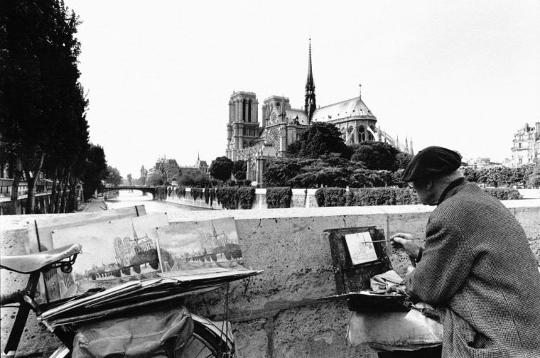 Image: A man paints the Notre Dame Cathedral.