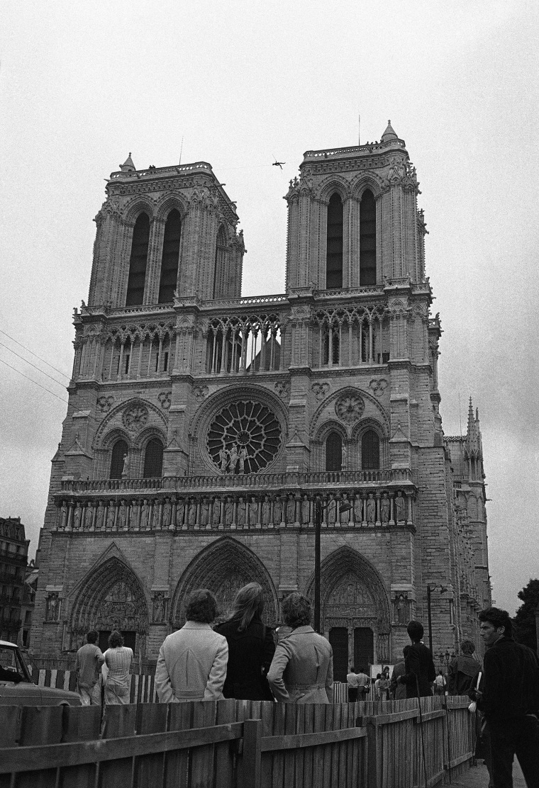 Image: People watch as Philippe Petit walks a tightrope 225 feet above the ground between the two towers of the Notre Dame Cathedral on June 26, 1971.