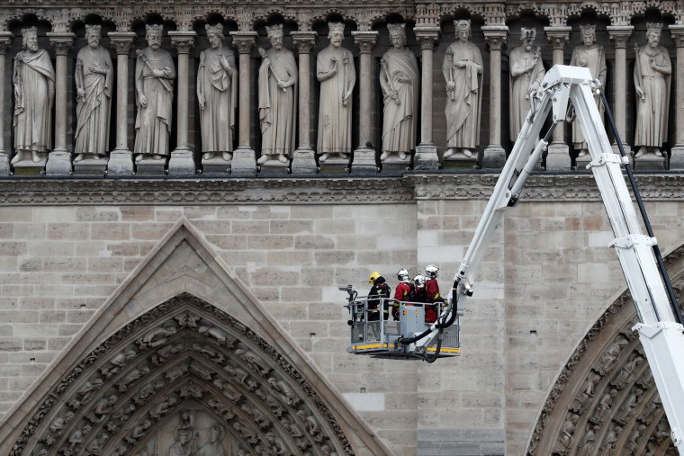 Image: Firefighters work at Notre-Dame Cathedral after a massive fire devastated large parts of the gothic gem in Paris
