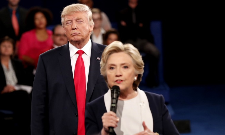 Image:Donald Trump listens as Hillary Clinton answers questions during a debate at Washington University in St. Louis, Missouri, on Oct. 9, 2016.